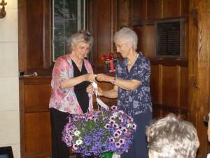 SOLF board member Deborah Costine presenting a basket of flowers to retiring board member Carol Gay for 25 years of service to SOLF.